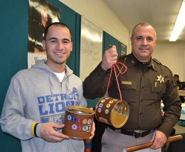 Macomb County Sheriff Anthony Wickersham and one of his mentor team members show off the bird feeders they made for their community service project.